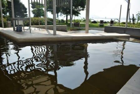 茶色の温泉がはられている。奥には諏訪湖が見える。